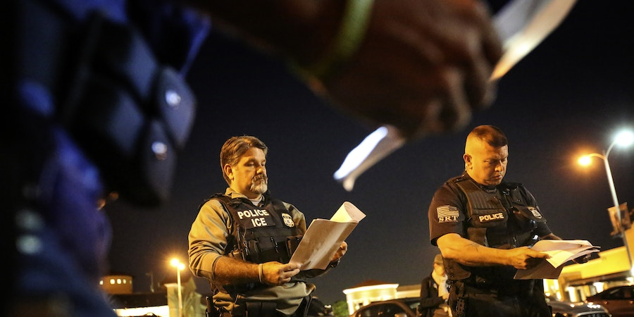 RIVERSIDE, CA - AUGUST 12: Jorge Field, left, and David Marin, both with ICE Enforcement and Removal Operations, getting briefed before getting out into the Riverside community to apprehend immigrants who may be deportable. Immigration and Customs Enforcement officials say they are relying more than ever on costly manhunts to locate immigrants in the country illegally who have criminal records. In the past, the agency would simply contact local jails where such immigrants were being detained and ask jail officials to hold them until an ICE van could pick them up, but hundreds of counties across the country stopped honoring such requests after a federal judge last year found that practice unconstitutional. (Irfan Khan/Los Angeles Times via Getty Images)