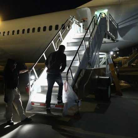 MESA, AZ - OCTOBER 15:  An undocumented immigrant boards an Immigration and Customs Enforcement (ICE), charter jet early on October 15, 2015 in Mesa, Arizona. The immigrants were to be flown to other states for follow-on ICE deportation flights to the Caribbean, Mexico and Central America. ICE builds deportation cases against thousands of undocumented immigrants, many of whom, they say, have criminal records. The number of ICE detentions and deportations has dropped in the last two years since some states adopted laws limiting how state law enforcement agencies cooperate with federal immigration authorities.  (Photo by John Moore/Getty Images)