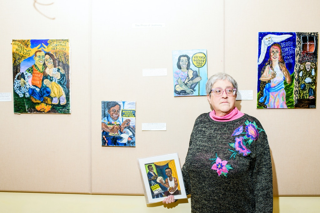 "Baltimore, Maryland - February 03, 2018: Painter Kimberly Sheridan stands for a portrait with her portraits at the ""Bridges for the Ones Left Behind"" gallery opening at the The Baltimore Ethical Society during the third Baltimore Ceasefire weekend Saturday February 3rd, 2018. She creates a series of painting of people killed by gun violence. CREDIT: Matt Roth"