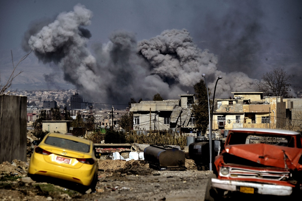 TOPSHOT - Smoke plumes rise after an airstrike in west Mosul on March 10, 2017 as Iraqi forces advance in the city during the ongoing battle to seize it from the jihadists of the Islamic State (IS) group. / AFP PHOTO / ARIS MESSINIS        (Photo credit should read ARIS MESSINIS/AFP/Getty Images)