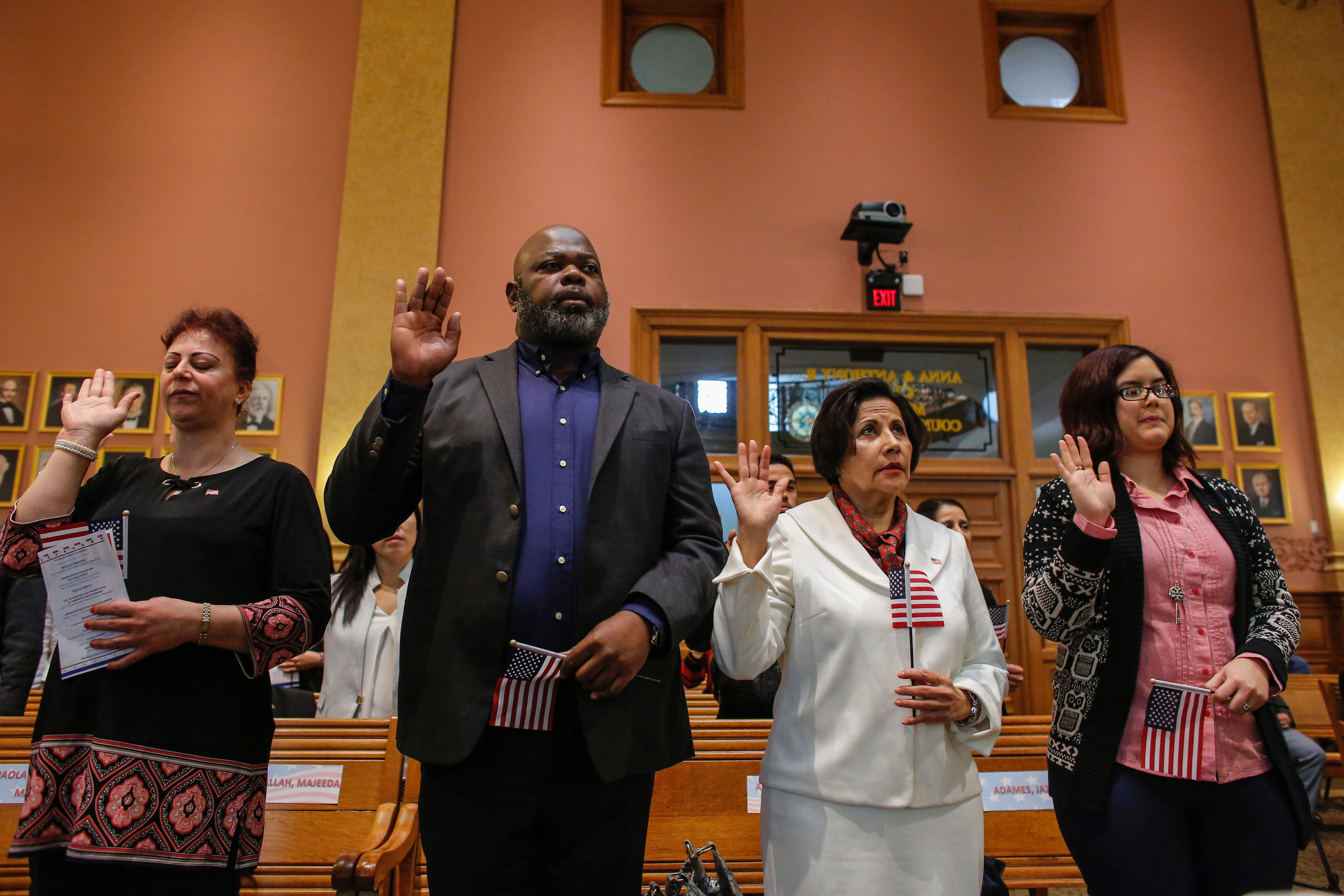 Candidates for US citizenship take the oath of allegiance during a Naturalization Ceremony for new US citizens at the City Hall of Jersey City in New Jersey  on February 22, 2017. / AFP / KENA BETANCUR        (Photo credit should read KENA BETANCUR/AFP/Getty Images)