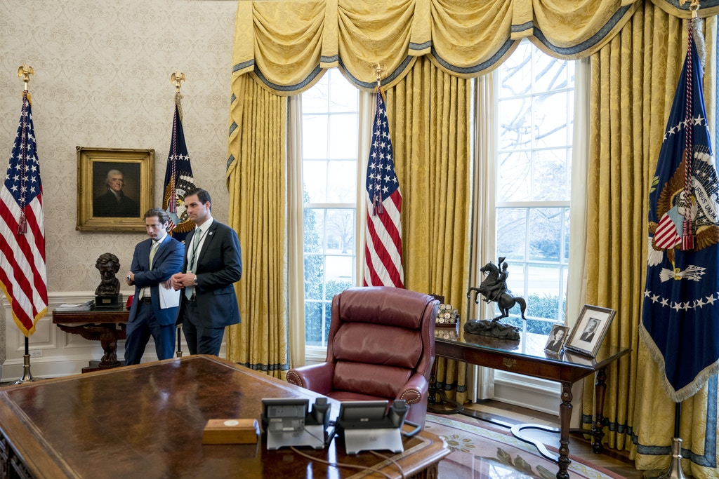 Treasury Secretary Steve Mnuchin's Chief of Staff Eli Miller, left, and White House Staff Secretary Rob Porter, right, stand in the Oval Office as President Donald Trump speaks at a tax reform meeting with American workers at the White House, Wednesday, Jan. 31, 2018, in Washington. (AP Photo/Andrew Harnik)