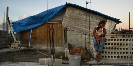 SAN ISIDRO, PUERTO RICO - DECEMBER 23:  Mother Isamar holds her baby Saniel, 9 months, at their makeshift home, under reconstruction, after being mostly destroyed by Hurricane Maria, on December 23, 2017 in San Isidro, Puerto Rico. Their neighborhood remains without electricity. Barely three months after Hurricane Maria made landfall, approximately one-third of the devastated island is still without electricity. While the official death toll from the massive storm remains at 64, The New York Times recently reported the actual toll for the storm and its aftermath likely stands at more than 1,000. A recount was ordered by the governor as the holiday season approached.  (Photo by Mario Tama/Getty Images)