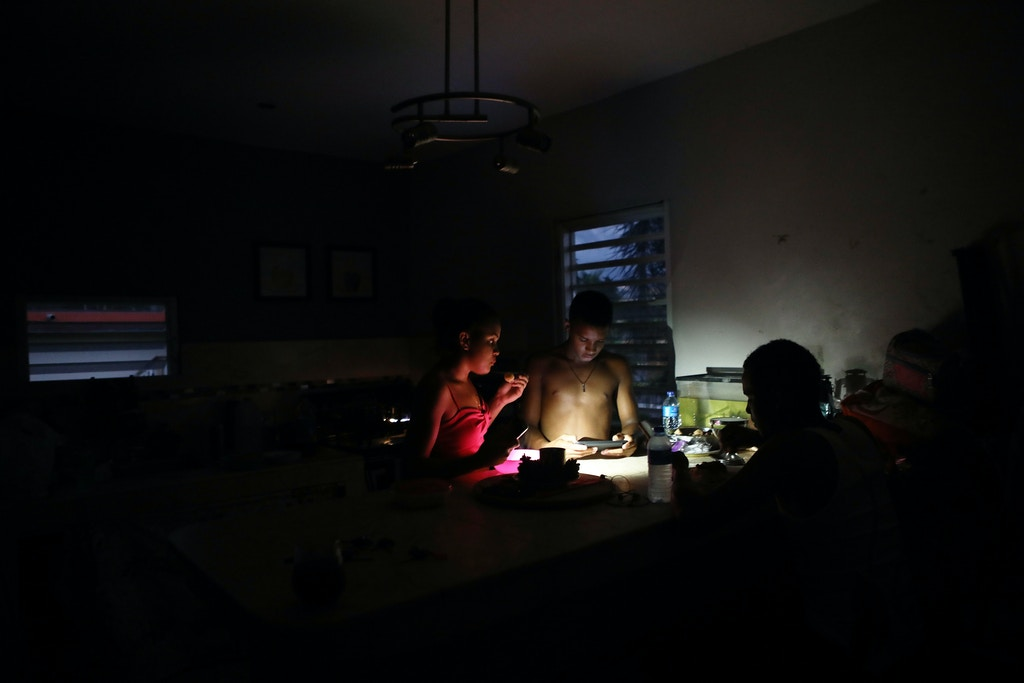 SAN ISIDRO, PUERTO RICO - DECEMBER 21:  Young members of the extended Medina family eat dinner at dusk with light from a cell phone on December 21, 2017 in San Isidro, Puerto Rico. The community was hard-hit by Hurricane Maria and remains mostly without grid electricity. Barely three months after Hurricane Maria made landfall, approximately one-third of the devastated island is still without electricity. While the official death toll from the massive storm remains at 64, The New York Times recently reported the actual toll for the storm and its aftermath likely stands at more than 1,000. Puerto Rico's governor has ordered a recount as the holiday season approaches.  (Photo by Mario Tama/Getty Images)