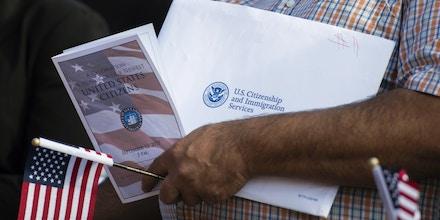 Imigrante segura documentos durante cerimônia de naturalização