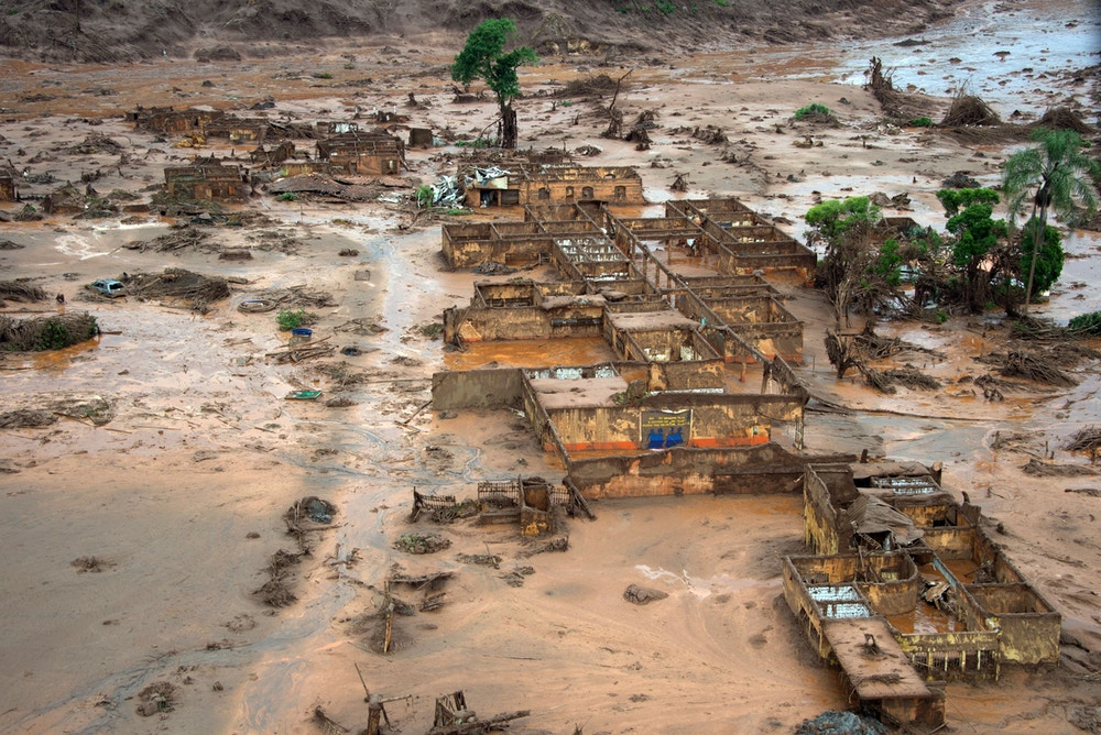 Aerial view of damages after a dam burst in the village of Bento Rodrigues, in Mariana, Minas Gerais state, Brazil on November 6, 2015. A dam burst at a mining waste site unleashing a deluge of thick, red toxic mud that smothered a village killing at least 17 people and injuring some 75. The mining company Samarco, which operates the site, is jointly owned by two mining giants, Vale of Brazil and BHP Billiton of Australia. AFP PHOTO /  CHRISTOPHE SIMON        (Photo credit should read CHRISTOPHE SIMON/AFP/Getty Images)