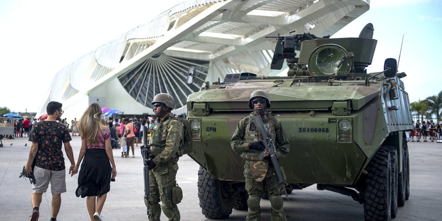 Brazilian marines with armoured personnel carriers (APC) stand guard at the Museum of Tomorrow area in the portuary zone of Rio de Janeiro, Brazil, on July 29, 2017. Brazil has mobilized some 8,500 soldiers to Rio de Janeiro state to fight organized crime and a spike in street violence. President Michel Temer signed a decree allowing the use of the armed forces in Rio de Janeiro state, the official government gazette announced. / AFP PHOTO / Mauro PIMENTEL (Photo credit should read MAURO PIMENTEL/AFP/Getty Images)