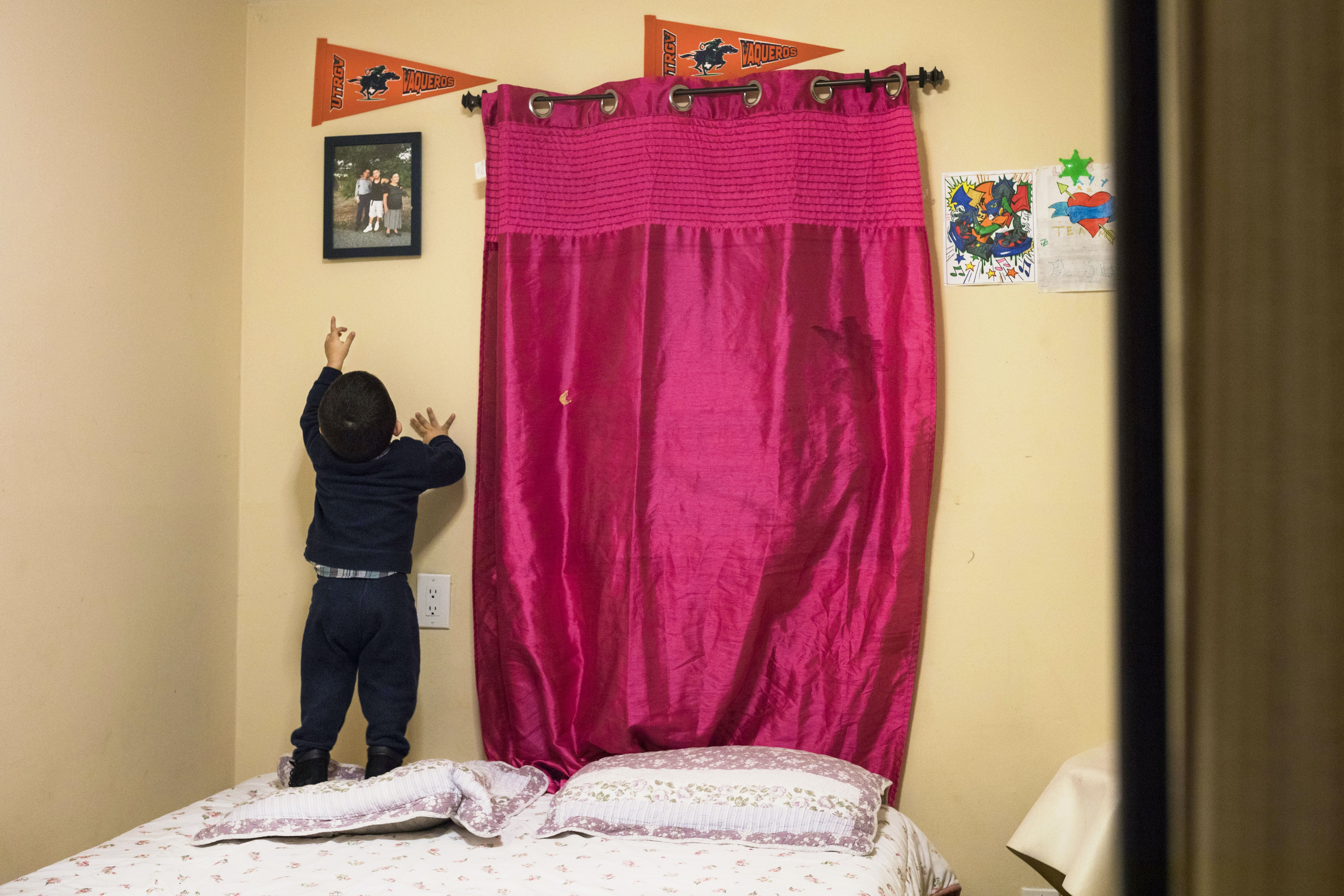 A view of Dennis's bedroom, where his little brother, 2, points up at a photo of Dennis and his grandmother in El Salvador, in Hempstead, Long Island on Oct. 19, 2017.