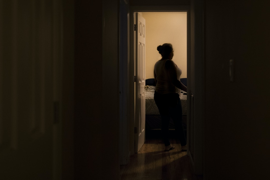 Laura, Dennis's mother, searches her house for belongings of her son while he is away in detention, in Hempstead, Long Island on Oct. 19, 2017.