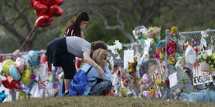 PARKLAND, FL - FEBRUARY 23:  Margarita Lasalle (L-R), the budget keeper, and Joellen Berman, Guidance Data Specialist, and Holli Sutton visit the memorial in front of Marjory Stoneman Douglas High School as teachers and staff are allowed to return to the school for the first time since the mass shooting on campus on February 23, 2018 in Parkland, Florida. Police arrested 19-year-old former student Nikolas Cruz for killing 17 people at the high school.  (Photo by Joe Raedle/Getty Images)