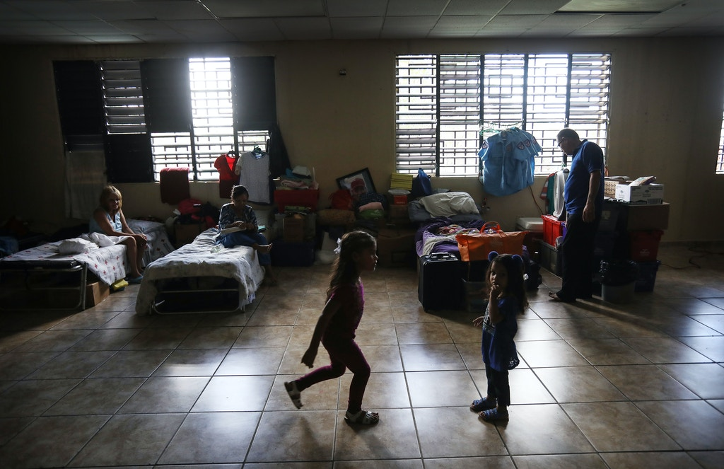 TOA BAJA, PUERTO RICO - DECEMBER 25:  Adults and children gather on Christmas day in the shelter for Hurricane Maria victims where they currently reside on December 25, 2017 in Toa Baja, Puerto Rico. 12 adults and 11 children currently reside in the shelter after losing their homes in the storm. Around 600 Hurricane Maria victims remain in shelters across Puerto Rico more than three months after Hurricane Maria made landfall. Thirty percent of the devastated island is still without electricity. While the official death toll from the massive storm remains at 64, The New York Times recently reported the actual toll for the storm and its aftermath likely stands at more than 1,000. A recount was ordered by the governor as the holiday season approached.  (Photo by Mario Tama/Getty Images)