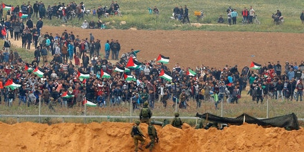 A picture taken on March 30, 2018 from the southern Israeli kibbutz of Nahal Oz across the border from the Gaza strip shows Palestinians participating in a tent city protest commemorating Land Day, with Israeli soldiers seen below in the foreground.Land Day marks the killing of six Arab Israelis during 1976 demonstrations against Israeli confiscations of Arab land. / AFP PHOTO / Jack GUEZ (Photo credit should read JACK GUEZ/AFP/Getty Images)