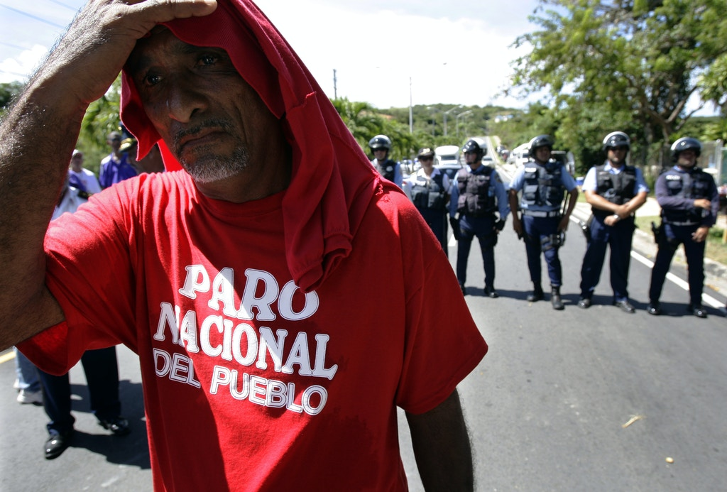 "A demonstrator wearing a T-shirt with the message in Spanish ""People's national strike"" gestures after police blocked a protest against Gov. Luis Fortuno near the hotel where Fortuno meets with foreign investors in Fajardo, eastern Puerto Rico, Thursday, Oct. 22, 2009. Demonstrators continue to protest the layoffs of more than 20,000 public employees, a measure the government says is necessary to close a deficit and pull the economy out of a three-year recession. (AP Photo/Andres Leighton)"