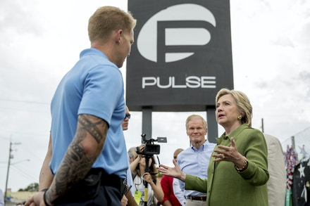 Democratic presidential candidate Hillary Clinton, accompanied by Sen. Bill Nelson, D-Fla., second from right, speaks with first responders as she visits a memorial outside of the Pulse nightclub in Orlando, Friday, July 22, 2016, which was the site of a June 12th shooting that kill 49 people. (AP Photo/Andrew Harnik)