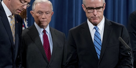 FBI Acting Director Andrew McCabe, right, accompanied by Attorney General Jeff Sessions, second from left, Deputy Attorney General Rod Rosenstein, takes the podium at a news conference to announce an international cybercrime enforcement action at the Department of Justice, Thursday, July 20, 2017, in Washington. (AP Photo/Andrew Harnik)