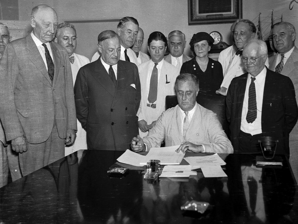 President Franklin D. Roosevelt signs the Social Security bill in Washington D.C. on Aug. 14, 1935. From left, are: Chairman Doughton of the House Ways and Means Committree; Sen. Wagner, D-N.Y, co-author of the bill, Secretary Perkins, Chairman Harrison of the Senate Finance Committe, Rep. Lewis, D-Md., co-author of the measure. (AP photo)