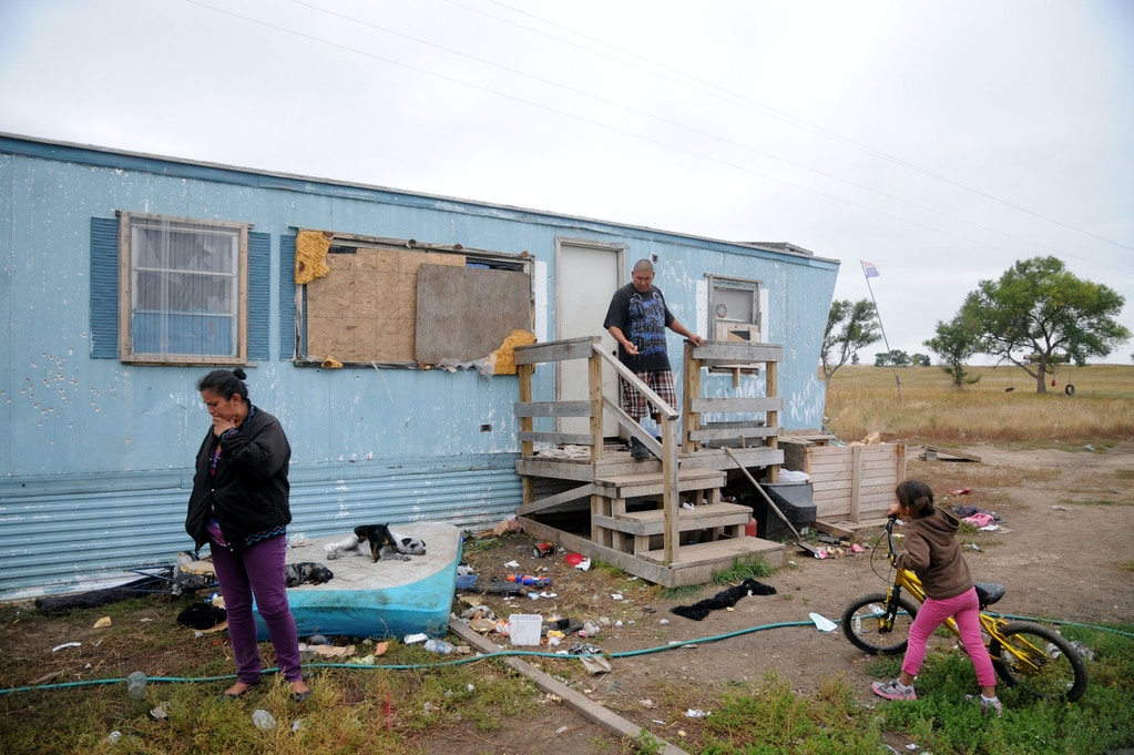 In this Wednesday, Sept. 30, 2015, photo, Natasha Cuny, left, her boyfriend, Raymond Eagle Hawk, center, and their daughter, Kimimila Eagle Hawk, right, stand outside Raymond Eagle Hawk's mother's trailer in Wounded Knee, S.D., on the Pine Ridge Indian Reservation. Cuny, Raymond Eagle Hawk and their daughter live next door in a shed. The housing shortage on South Dakota's Pine Ridge Indian Reservation is a longstanding problem for thousands of Oglala Sioux members, but the tribe is pushing the issue into the spotlight again after severe storms and flooding in May spurred a federal disaster declaration. (AP Photo/James Nord)