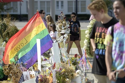 Mourners visit a makeshift memorial, in front of the Dr. Phillips Center for the Performing Arts, for victims of the Pulse nightclub shooting, Saturday, June 25, 2016, in Orlando, Fla. (Phelan M. Ebenhack via AP)