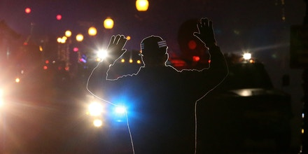 FERGUSON, MO - NOVEMBER 24:  A protester stands in front of police vehicles with his hands up during a demonstration on November 24, 2014 in Ferguson, Missouri. A St. Louis County grand jury has decided to not indict Ferguson police Officer Darren Wilson in the shooting of Michael Brown that sparked riots in Ferguson, Missouri in August.  (Photo by Justin Sullivan/Getty Images)