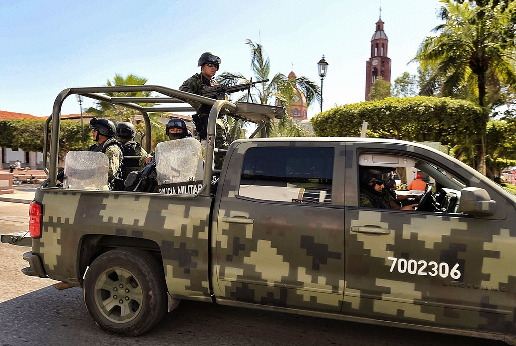 Mexican soldiers patrol the streets of Apatzingan community, state of Michoacán, on January 10, 2015. A deadly clash erupted on January 6th between federal forces and civilians in Apatzingan, a former Knights Templar stronghold. Officials say at least nine people died after federal police and soldiers took back control of the City Hall from a group that had been occupying it since last December. AFP PHOTO/Alfredo ESTRELLA        (Photo credit should read ALFREDO ESTRELLA/AFP/Getty Images)