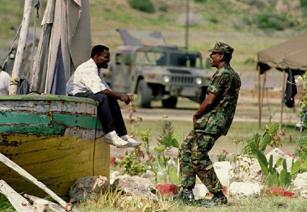 GUANTANAMO BAY, CUBA:  Cuba: Haitian refugee Sony Eskite (L) and Naval Petty Officer Carl Vincent (R) laugh 14 June at Camp Bulkeley as 27 HIV-positive Haitian refugees were transported to the U.S.  Eskite and the 113 remaining Haitians are scheduled to be transported to the U.S. (Photo credit should read ROBERT SULLIVAN/AFP/Getty Images)