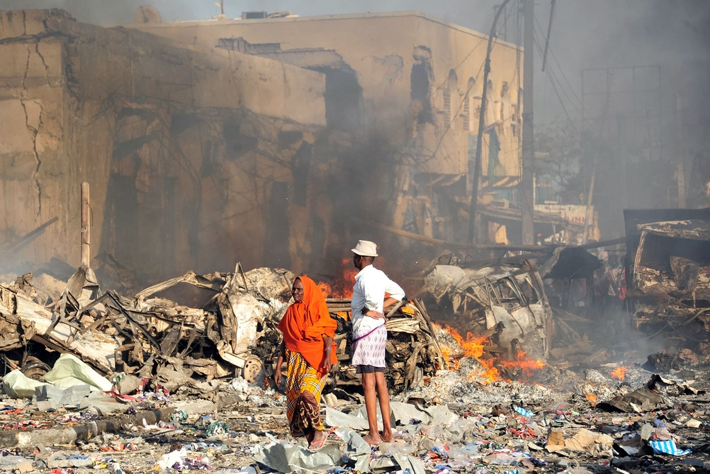 TOPSHOT - A man and woman look at the damages on the site of the explosion of a truck bomb in the centre of Mogadishu, on October 14, 2017.A truck bomb exploded outside a hotel at a busy junction in Somalia's capital Mogadishu on October 14, 2017 causing widespread devastation that left at least 20 dead, with the toll likely to rise. / AFP PHOTO / Mohamed ABDIWAHAB (Photo credit should read MOHAMED ABDIWAHAB/AFP/Getty Images)