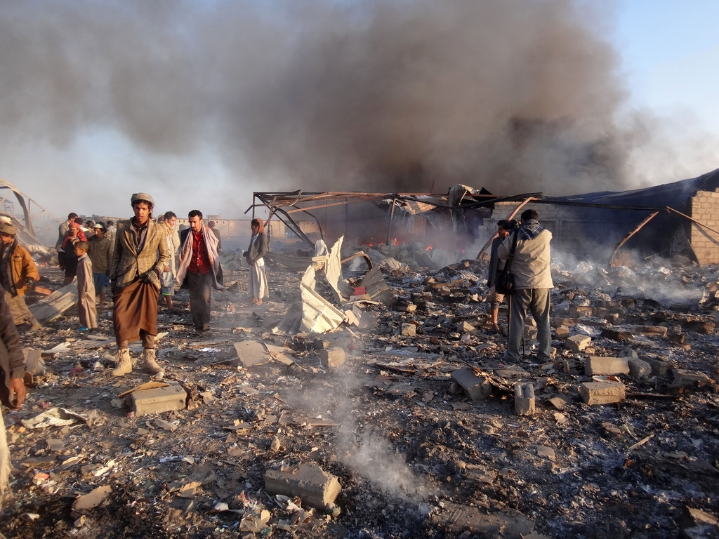 Smoke rises as Yemenis inspect the damage at the site of air strikes in the northwestern Huthi-held city of Saada, on January 6, 2018. / AFP PHOTO / STRINGER        (Photo credit should read STRINGER/AFP/Getty Images)