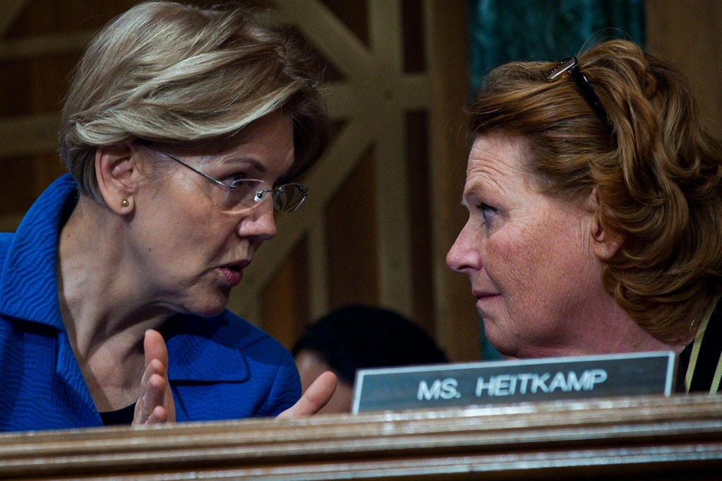 WASHINGTON, DC - JANUARY 30:  Senators Elizabeth Warren (D-MA) and Heidi Heitkamp (D-ND) confer during a hearing where Treasury Secretary Steven Mnuchin delivered the annual financial stability report to the Senate Banking, Housing and Urban Affairs Committee on January 30, 2018 in Washington, DC. Mnuchin said the Treasury can extend the government's debt limit suspension period into February before it exhausts its borrowing ability.  (Photo by Pete Marovich/Getty Images)