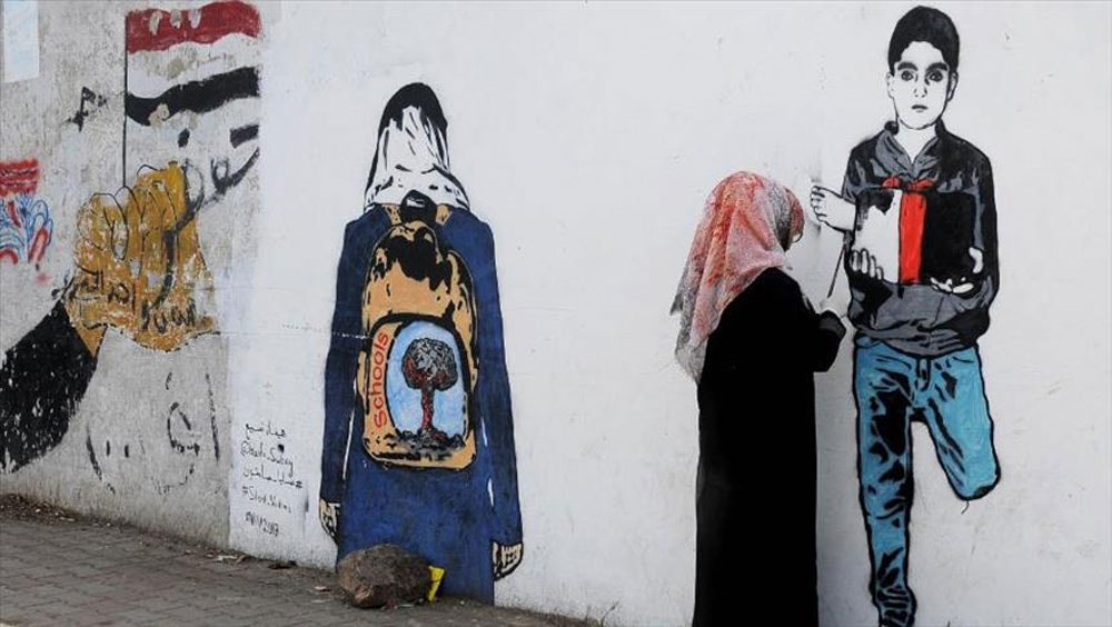 Yemeni street artist Haifa Subay paints a mural in Sana'a, Yemen. Photo: Courtesy of Haifa Subay