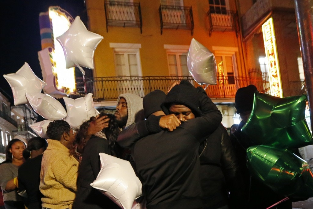 People gather for a vigil at Bourbon Street and Iberville Street for Demontris Toliver, who was killed in a shooting in the early morning, in the French Quarter section of New Orleans, Sunday, Nov. 27, 2016. Police had already increased patrols in New Orleans' bustling French Quarter before gunfire erupted early Sunday, leaving at least one man dead and several other people wounded in the tourist district known for its bars, bright lights and live music. (AP Photo/Gerald Herbert)