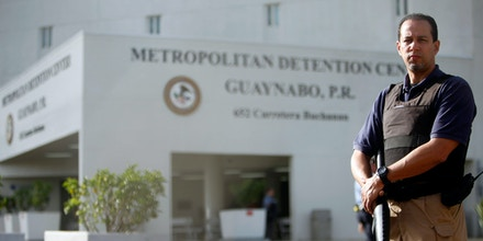 A federal corrections officer looks on while holding a weapon inside the prison while protestors sit in front of the main entrance of the Metropolitan Detention Center while demanding the freedom of jailed pro-independence activist Oscar Lopez Rivera in Guaynabo, Puerto Rico, Monday, July 8, 2013. Lopez was sentenced to 55 years after his conviction in 1981 on charges that included seditious conspiracy, use of force to commit robbery and interstate transportation of firearms as a member of the ultranationalist Armed Forces of National Liberation in a struggle for independence from the U.S. for the Caribbean island. He received an additional 15 years in 1988 after he was convicted of conspiring to escape from prison in Leavenworth, Kansas. Former President Bill Clinton offered in 1999 to release Lopez and 13 other Puerto Rican nationalists as part of what was at the time a politically sensitive clemency deal. Under the deal, Lopez would have had to serve 10 more years in prison. He rejected the offer because it did not include two comrades who have since been released. (AP Photo/Ricardo Arduengo)