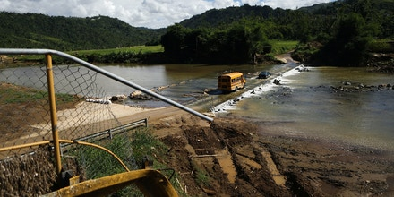 MOROVIS, PUERTO RICO - DECEMBER 20:  A school bus crosses a makeshift bridge for vehicles, near where the original bridge was washed away by Hurricane Maria flooding, on December 20, 2017 in Morovis, Puerto Rico. Barely three months after Hurricane Maria made landfall, approximately one-third of the devastated island is still without electricity and 14 percent lack running water. While the official death toll from the massive storm remains at 64, the New York Times recently reported the actual toll for the storm and its aftermath likely stands at more than 1,000. Puerto Rico's governor has ordered a review and recount as the holiday season approaches.  (Photo by Mario Tama/Getty Images)