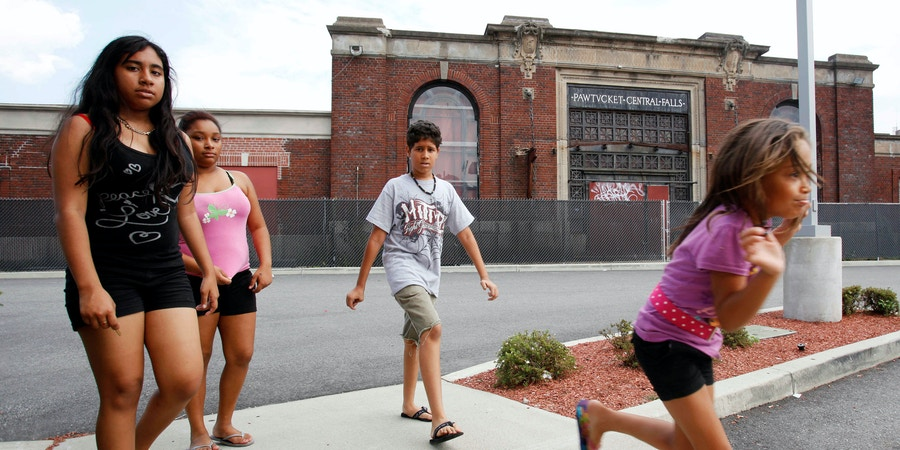 Children in Central Falls, R.I., walk past the boarded-up railroad terminal, Tuesday, Aug. 2, 2011. The communities surrounding Central Falls are watching their neighbor's municipal bankruptcy with caution as they consider stepping in to share services while trying to ensure they aren't the next to be declared insolvent. (AP Photo/Michael Dwyer)