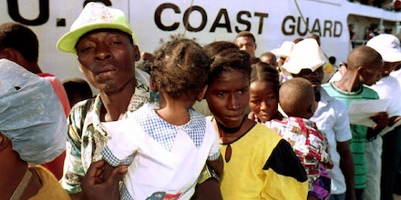 PORT-AU-PRINCE, HAITI:  Jean Pierre (L) and Denisse Joseph (R) disembark with their 10-month-old child (C) after they were brought back to Haiti 16 January, 1993 aboard the U.S Coast Guard ship ''Independence
