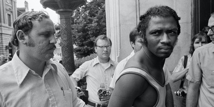 FILE- In this Sept. 1, 1973 file photo, Herman Bell, right, glares at the media following his arrest in New Orleans. The former member of the Black Liberation Army, who was convicted of fatally shooting two New York City police officers in 1971, has been granted parole and will be realized from Shawangunk Prison on April 17, 2018. (AP Photo)