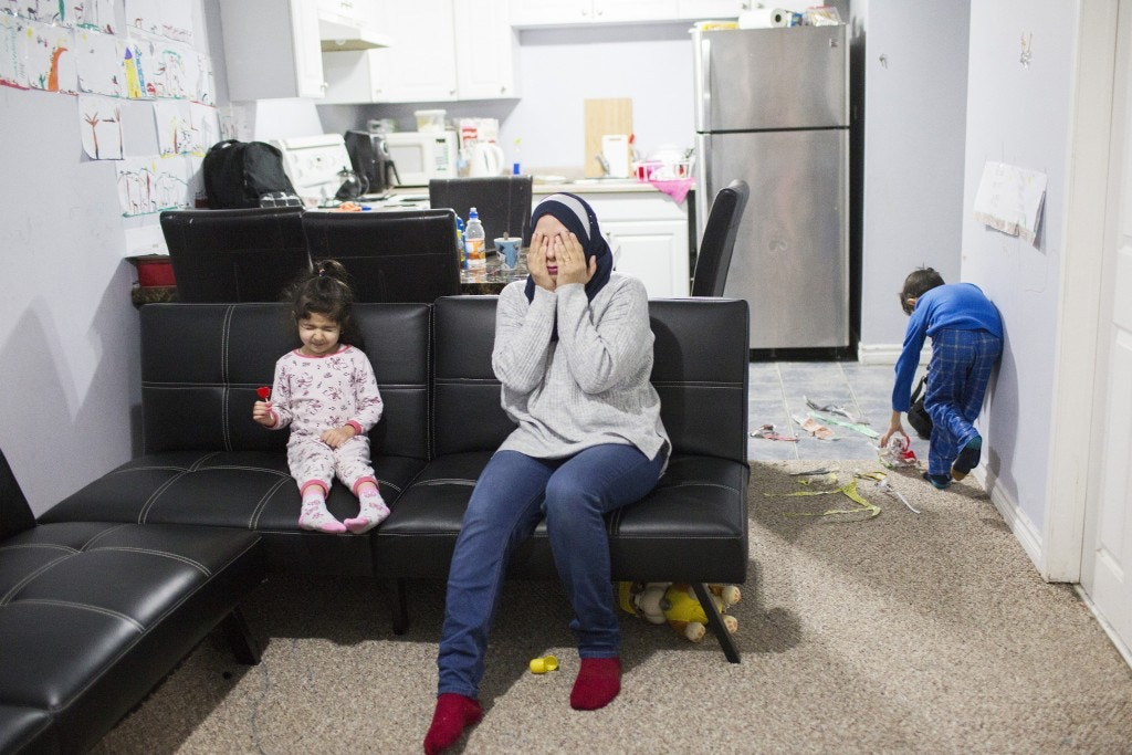 Shia Iraqi refugee Zinah Al shakarchi (centre) who has been separated from her husband after he was denied asylum in America and is being held at a detention center in Texas, with her children Sidrah, 3, (left) and Yousif, 6, (right) in the apartment where they have lived for one month in Mississauga, Ontario on Sunday, Jan. 14, 2018. The family were expelled from the UAE in 2016 along with hundreds of other Shia Iraqis and they have been displaced to Georgia, Mexico, and the United States before Zinah and her children received asylum in Canada. (Michelle Siu for The Intercept)