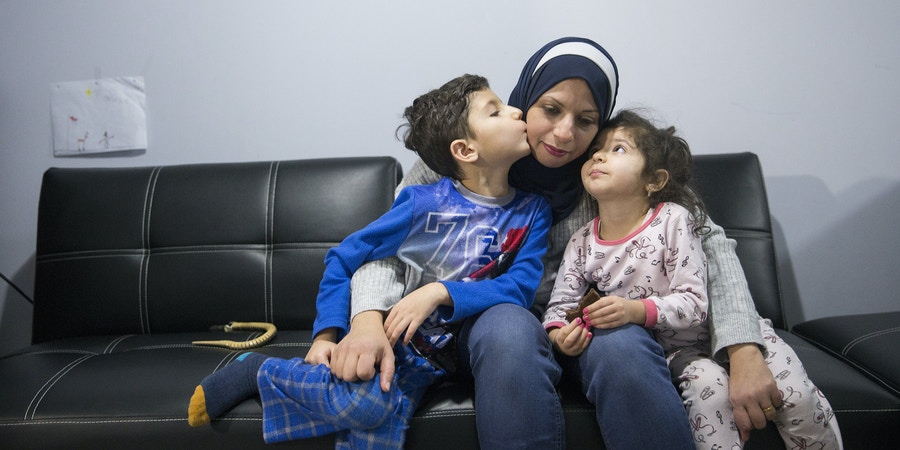 Shia Iraqi refugee Zinah Al shakarchi, centre, who has been separated from her husband after he was denied asylum in America and is being held at a detention center in Texas, with her son Yousif, 6, left, and daughter Sidrah, 3, right, in their basement apartment in Mississauga, Ontario on Sunday, Jan. 14, 2018. The family were expelled from the UAE in 2016 along with hundreds of other Shia Iraqis and they have been displaced to Georgia, Mexico, and the United States before Zinah and her children received asylum in Canada. (Michelle Siu for The Intercept)