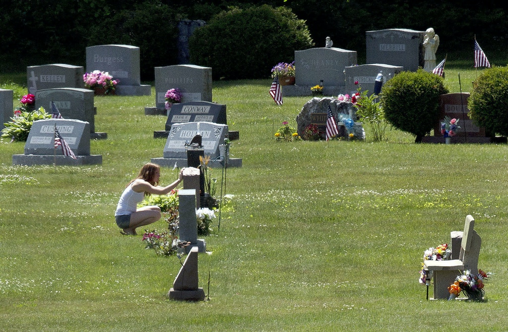 FILE - In this June 17, 2016 file photo, Erika Marble visits the gravesite of Edward Martin III, her fiancé and father of her two children, in Littleton, N.H. The 28-year old died Nov. 30, 2014, from an overdose of the opioid Fentanyl. Drug overdose deaths increased by 33 percent in the past five years across the U.S. as of 2016. New Hampshire saw a 191 percent increase while Massachusetts, North Dakota, Connecticut and Maine saw death rates jump by more than 100 percent.[AP Photo/Jim Cole, File)
