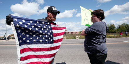 FLINT, MI - SEPTEMBER 14: A pro-Trump supporter (left) and an anti-Trump protestor (right) have a discussion while waiting for Republican presidential nominee Donald Trump to arrive for a tour of the Flint Water Treatment Plant September 14, 2016 in Flint, Michigan. While in Flint, Trump will also meet with several ministers from the area.  (Photo by Bill Pugliano/Getty Images)