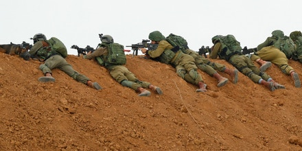 Israeli soldiers take aim as they lie prone over an earth barrier along the border with the Gaza strip in the southern Israeli kibbutz of Nahal Oz on March 30, 2018, as Palestinians demonstrate on the other side commemorating Land Day.Land Day marks the killing of six Arab Israelis during 1976 demonstrations against Israeli confiscations of Arab land. / AFP PHOTO / Jack GUEZ (Photo credit should read JACK GUEZ/AFP/Getty Images)
