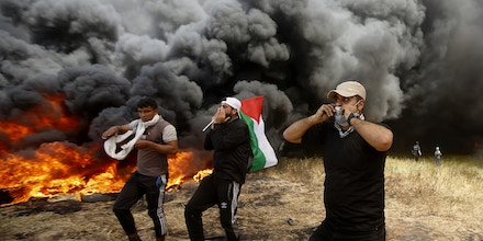 Palestinian protesters chant slogans next to burning tires during clashes with Israeli troops along Gaza's border with Israel, east of Khan Younis, Gaza Strip, Friday, April 6, 2018. Palestinians torched piles of tires near Gaza's border with Israel on Friday, sending huge plumes of black smoke into the air and drawing Israeli fire that killed one man in the second large protest in the volatile area in a week. (AP Photo/Adel Hana)