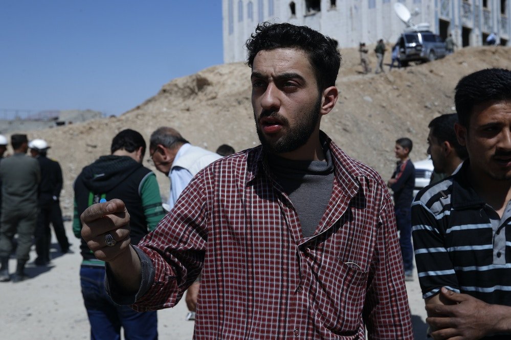 In this Monday, April 16, 2018 photo, Kahled Mahmoud Nuseir, 25, who lost his wife, Fatmeh Karout nine months pregnant and daughters Qama 18 months and Nour two and half years, during the alleged chemical weapons attack occurred speaks during an interview with the Associated Press in front of a hospital that locals referred as Point One, background, just meters away from where in the town of Douma, the site of a suspected chemical weapons attack, near Damascus, Syria. The survivors blamed the attack on the Army of Islam, the powerful rebel group that controlled the town before it was taken over by Syrian government forces this week, although they did not offer evidence to back up their claims. (AP Photo/Hassan Ammar)