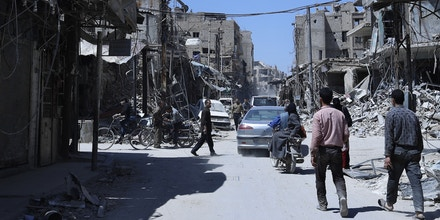 People walk in the town of Douma, the site of a suspected chemical weapons attack, near Damascus, Syria, Monday, April 16, 2018.  Two days after Syrian troops declared Douma liberated from opposition fighters, a tour in the city showed the wide destruction it has suffered since falling under rebel control six years ago. (AP Photo/Hassan Ammar)