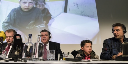 (From L) Russian ambassador in The Netherlands Aleksander Shulgin (L), Syrian deputy representative at the Organisation for the Prohibition of Chemical Weapons (OPCW) Ghassan Obaid, a Syrian boy (appearing on the video above) and a Syrian man attend a press conference in The Hague on April 26, 2018 called by Russian embassy to present what it says are witnesses 'used to stage' Douma attack videos. - Russian diplomats said they are organising the briefing for OPCW member nations and would