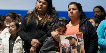 Esmeralda Baustista holds her daughter and a photograph of her brother Luis Bautista-Martinez, one of the workers detained when ICE raided Southeastern Provisions, at a prayer vigil on April 9, 2018 at Hillcrest Elementary School in Morristown, Tennessee.