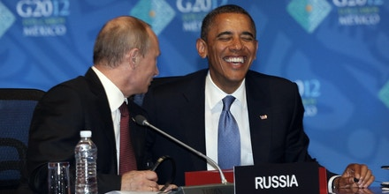 U.S. President Barack Obama, right, reacts while listening to Russia's President Vladimir Putin before the opening of the first plenary session of the G-20 Summit in Los Cabos, Mexico, Monday, June 18, 2012. (AP Photo/Andres Leighton)
