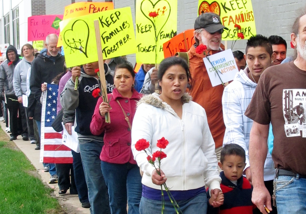 Supporters of immigration reform walk through downtown Cedar Rapids, Iowa, on Friday, May, 10, 2013, to mark the five-year anniversary of the immigration raid at the Agriprocessors plant in Postville. (AP photo/Ryan J. Foley)