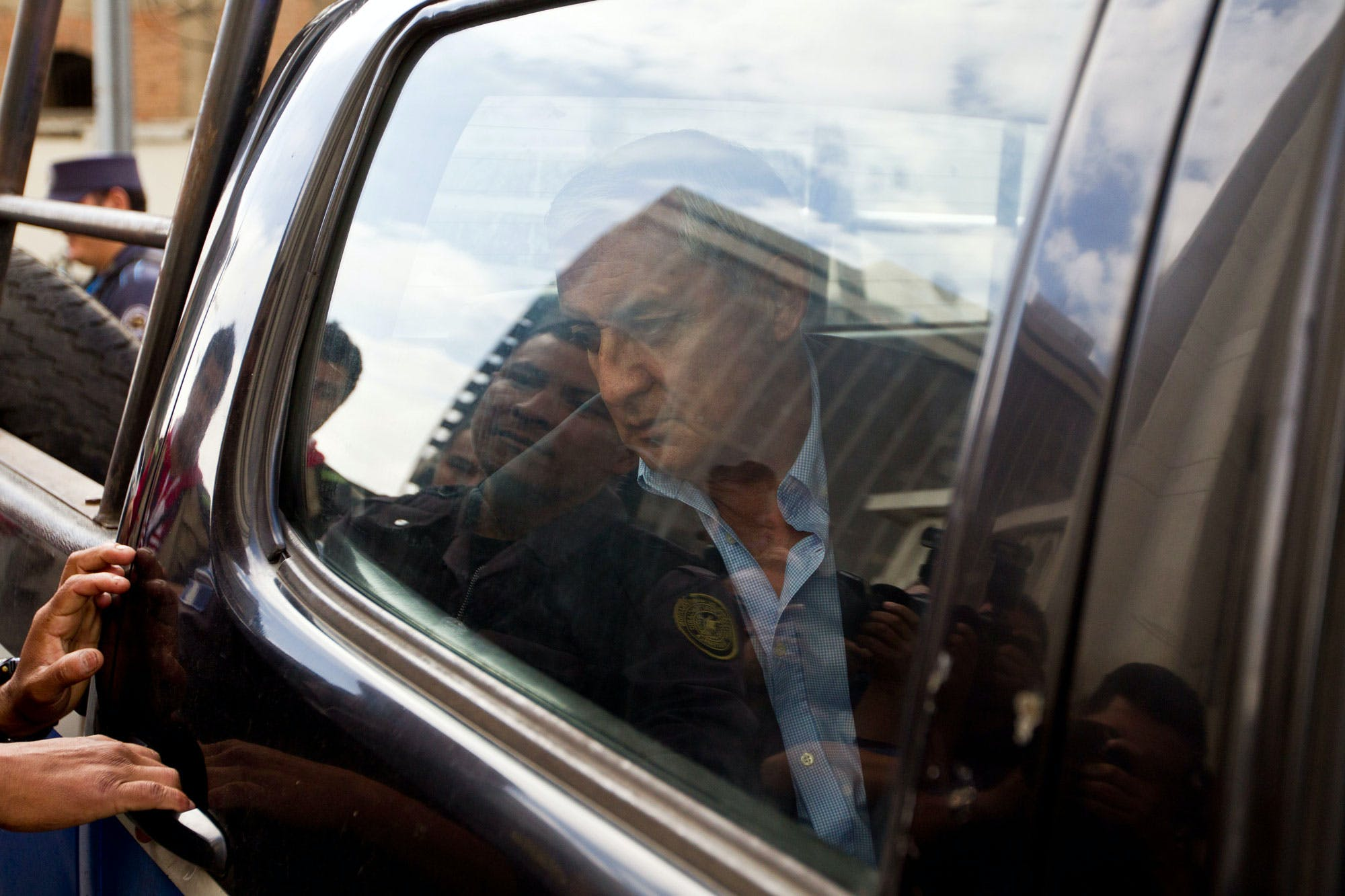 Guatemalan former President Otto Perez Molina arrives in a police vehicle to a court hearing in Guatemala City, Monday, June 13, 2016. The ex-president faces charges of money laundering and conspiracy. Three senior Guatemalan cabinet, all who served under Perez Molina, were arrested Saturday on corruption charges, and authorities said they were seeking to detain two more as part of a continuing crackdown that has seen the former president and his vice president jailed. (AP Photo/Moises Castillo)