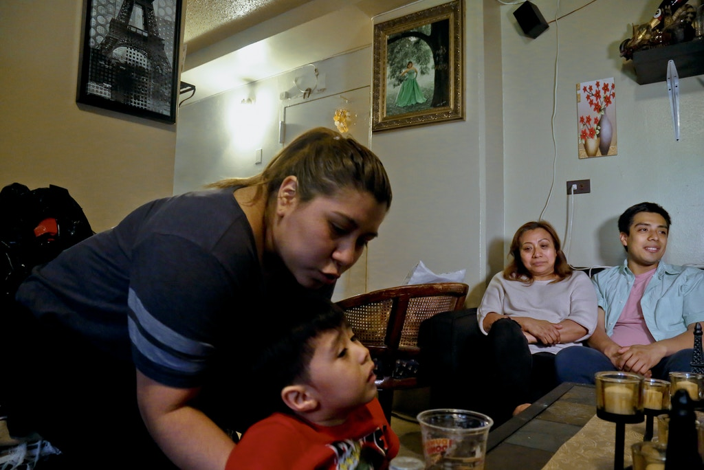 In this Wednesday May 17, 2017 photo, Rosa, second from right, an undocumented immigrant who wants her family's last name withheld, is surrounded by her son Edgar, far right, daughter Olga, far left, and grandson Logan at their home during an interview in New York. Rosa who used to get about $190 per month from the Supplemental Nutrition Assistance Program or SNAP, stopped taking benefits fearing deportation, and now gets by with the help of a local church and some family members. (AP Photo/Bebeto Matthews)