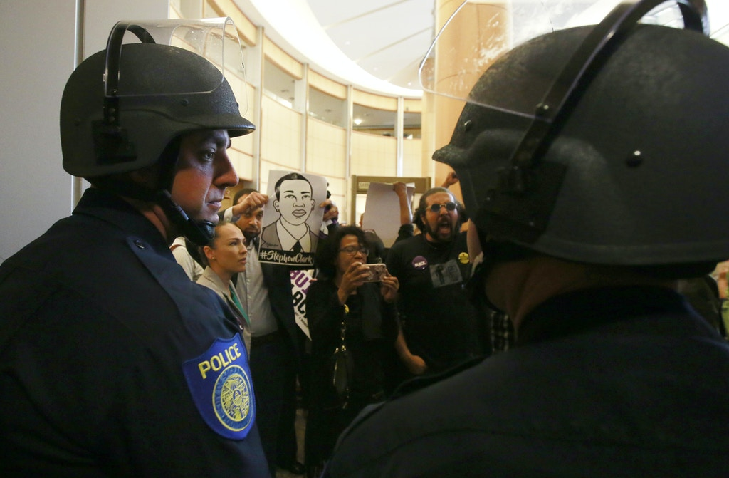 Helmeted Sacramento Police officers block the entrance to the Sacramento City Council chambers from demonstrators protesting the shooting death of Stephon Clark by Sacramento Police, Tuesday, March 27, 2018, in Sacramento, Calif. Clark, who was unarmed, was shot and killed a week earlier by two officers responding to a call about a person smashing car windows. (AP Photo/Rich Pedroncelli)